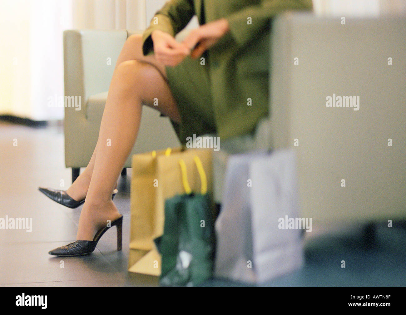 Woman in heels sitting, shopping bags on floor to the side, lower section - Stock Image