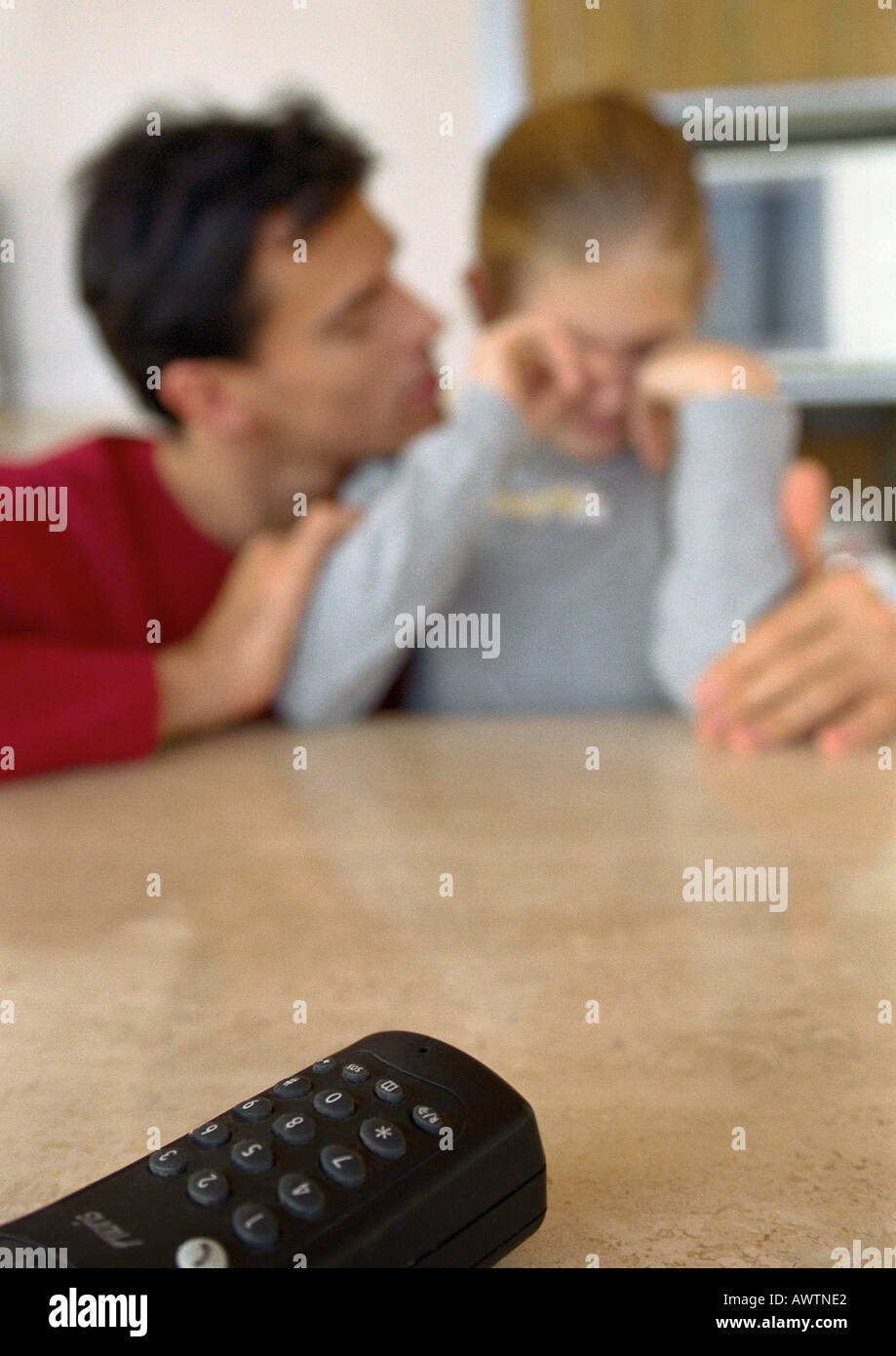 Remote control on table, father and daughter in background, blurred. - Stock Image