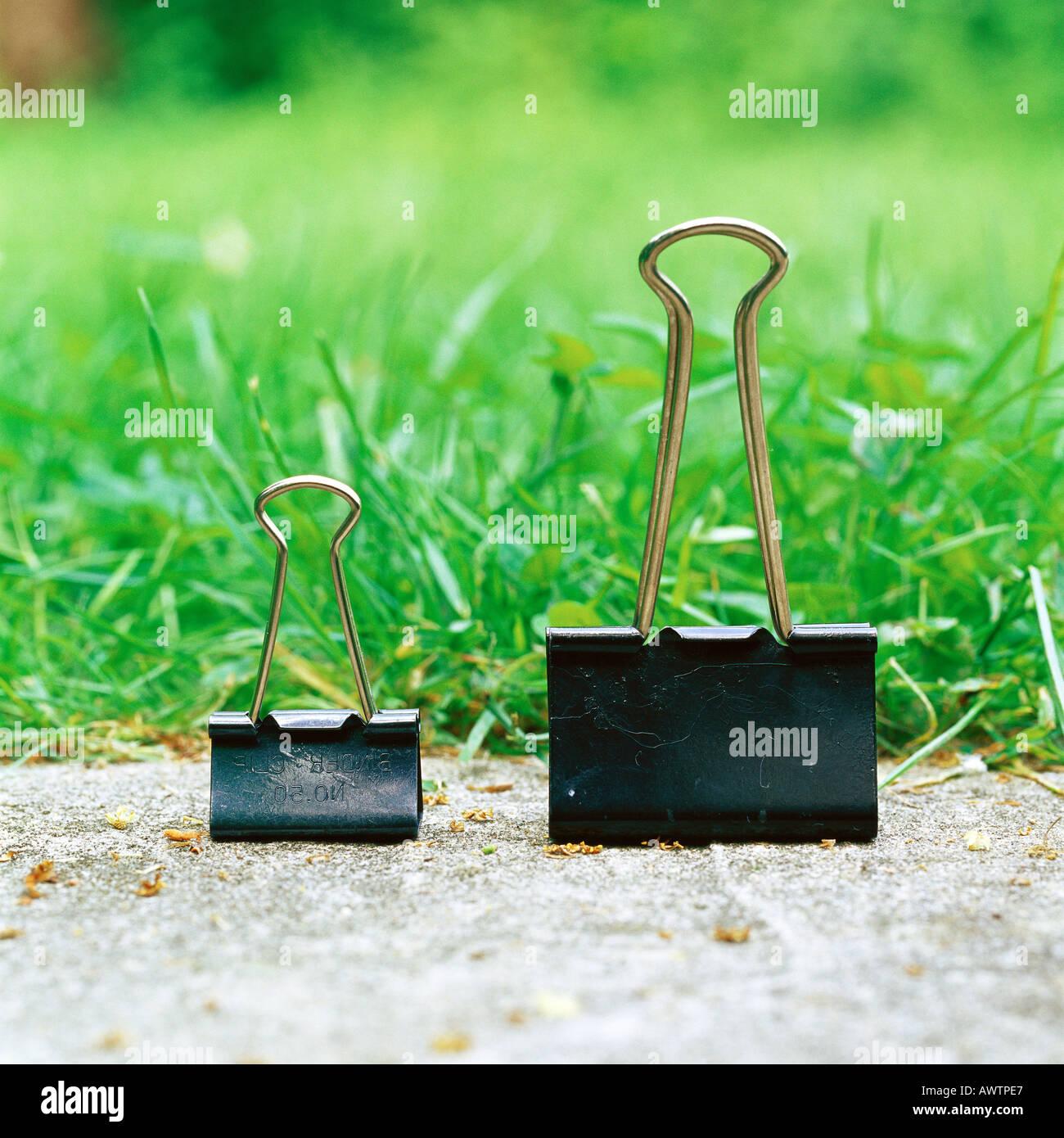 Binder clips on sidewalk - Stock Image
