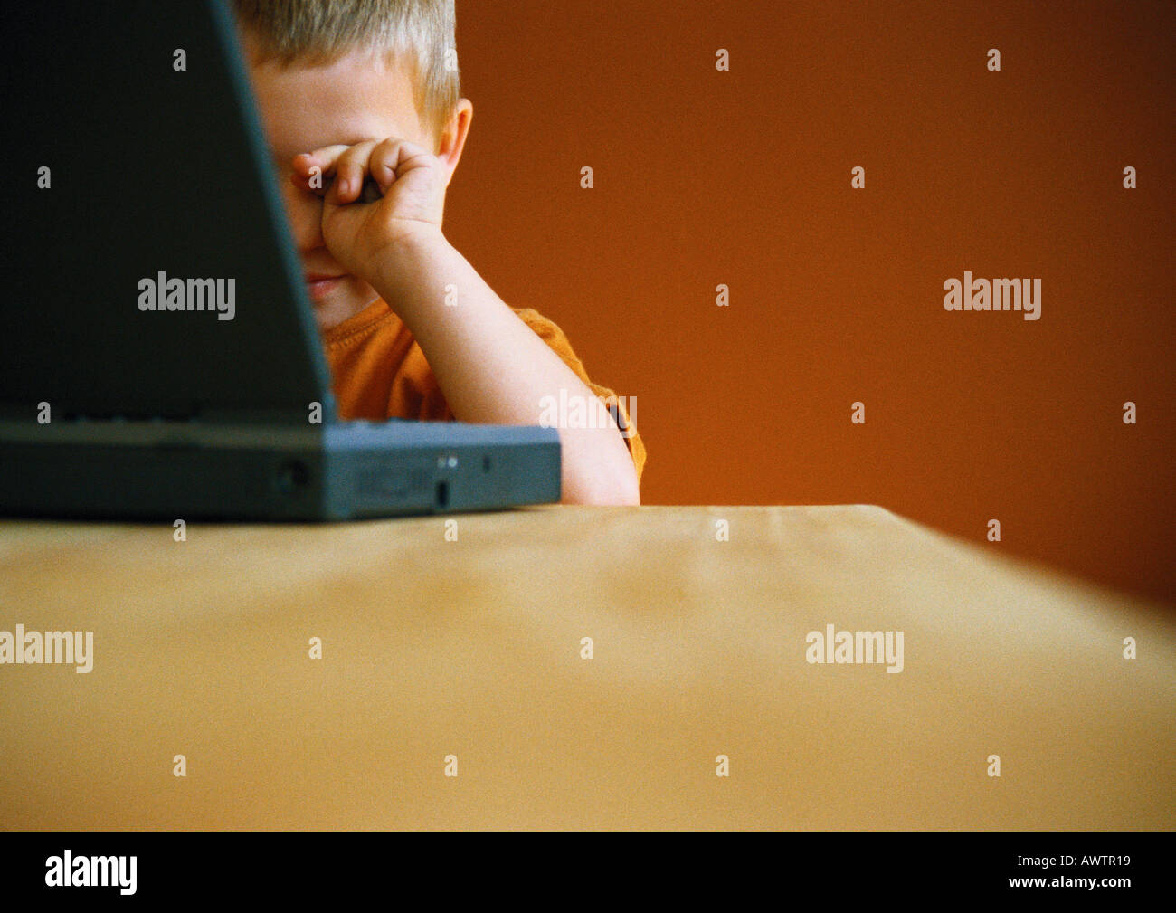 Little boy with laptop, rubbing eyes - Stock Image