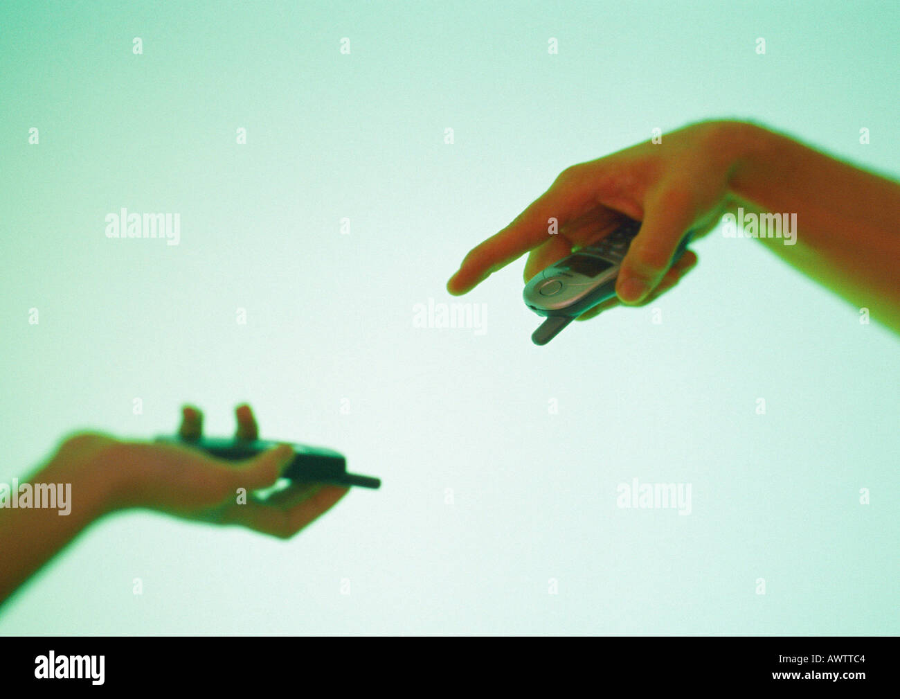Two hands holding cell phones, one gesturing to other - Stock Image