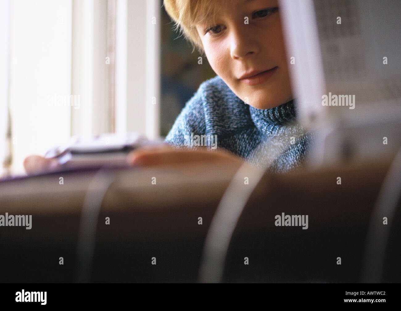 Young boy looking at video game, close up, computer and desk blurred in foreground - Stock Image