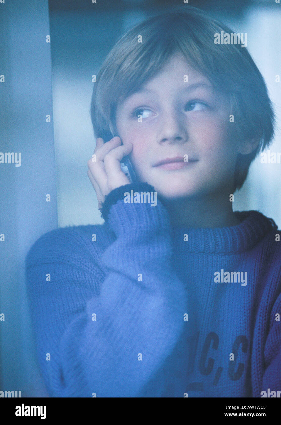 Young boy talking on phone, looking out window, portrait - Stock Image