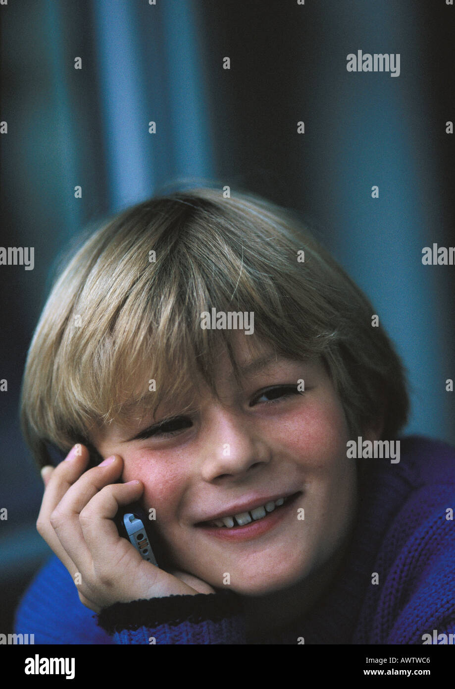 Young boy on phone, smiling, close up - Stock Image