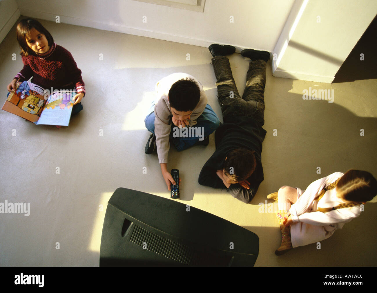 Young boys and girls sitting on floor watching TV, high angle view - Stock Image