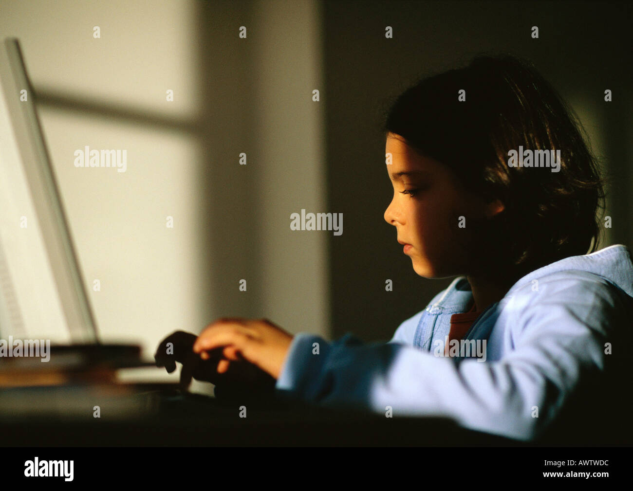 Young girl sitting, typing on laptop - Stock Image
