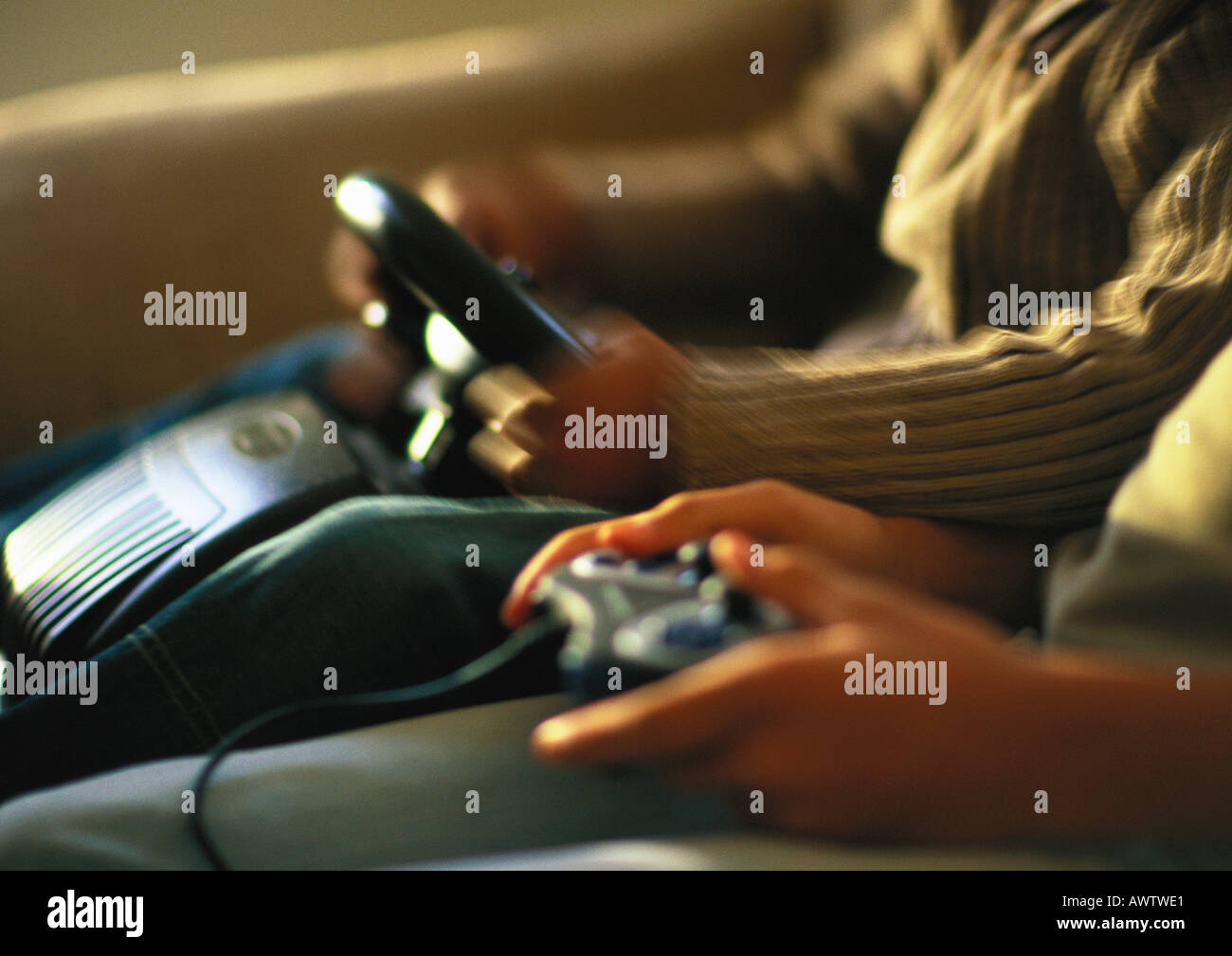 Hands of children playing video game, close up - Stock Image