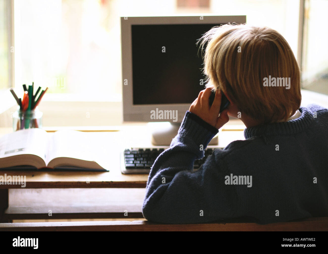 Young boy sitting at computer talking on phone, rear view - Stock Image