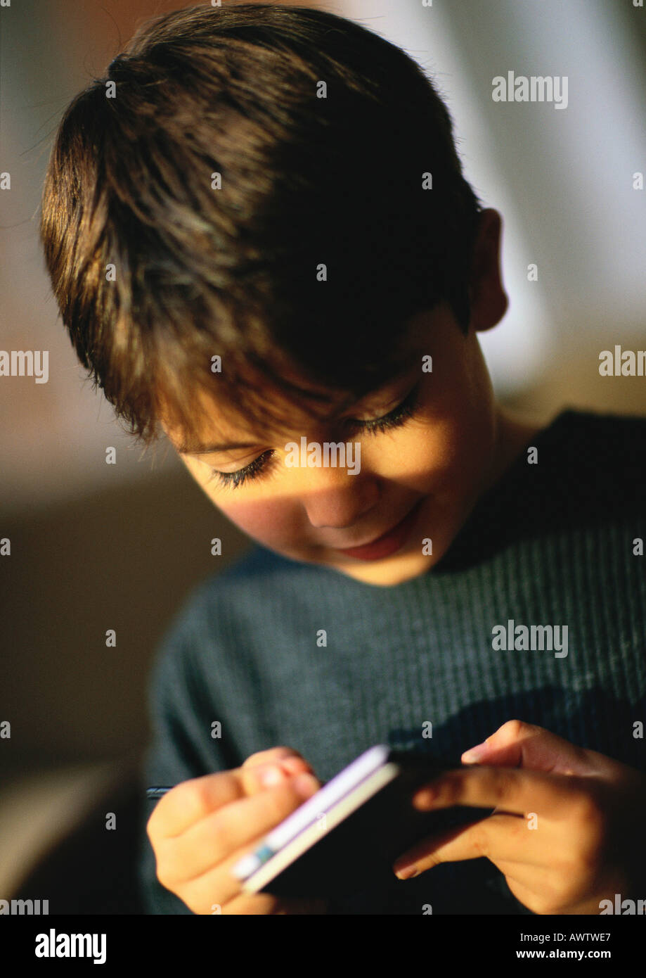 Young boy playing with hand held personal assistant, close up - Stock Image