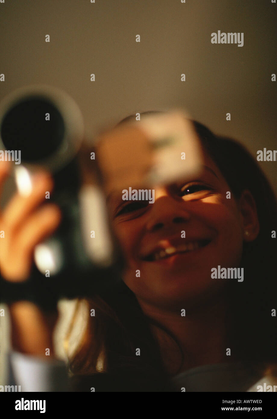Young girl with camera, smiling, close up - Stock Image