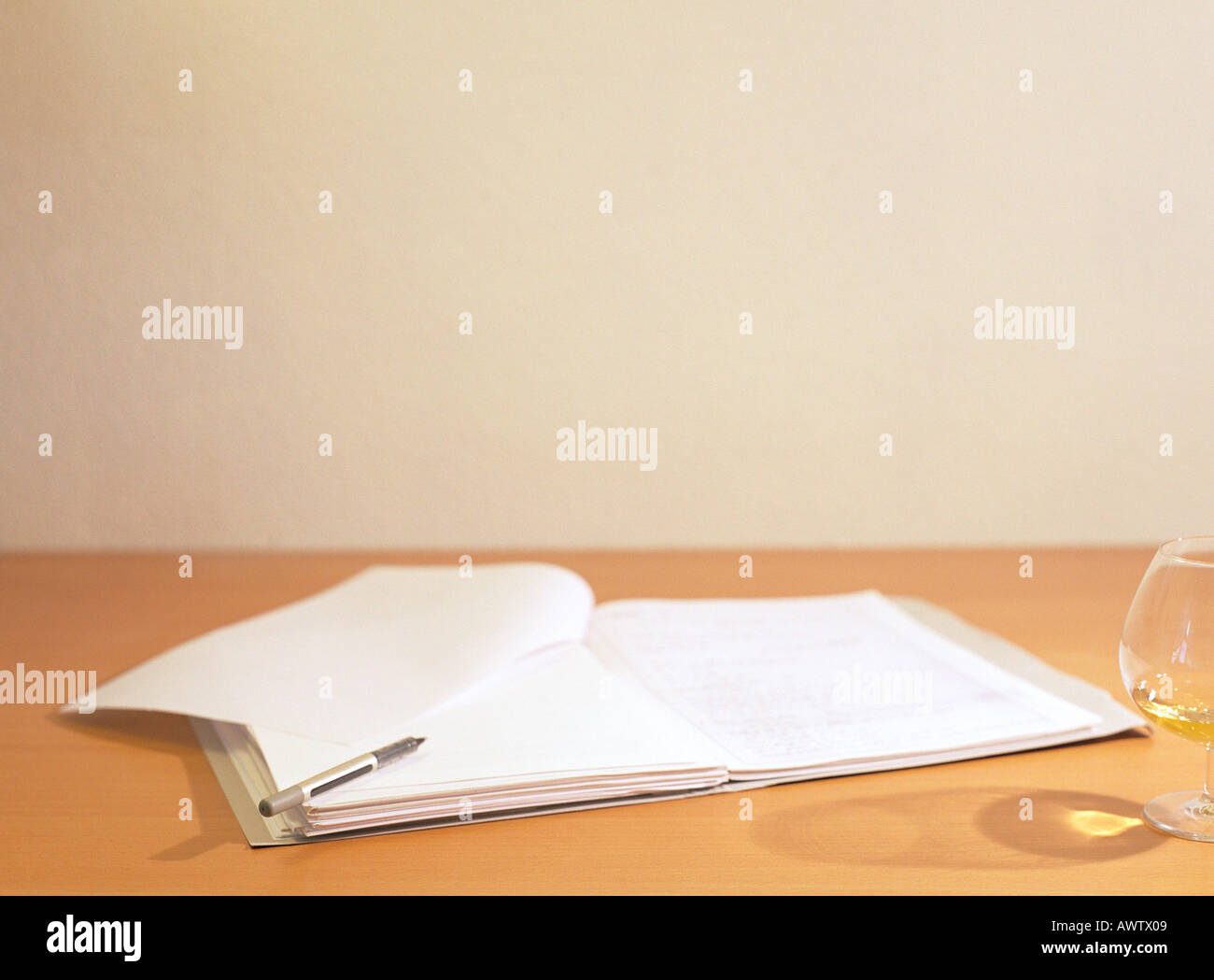 Pen and open book on desk next to glass - Stock Image