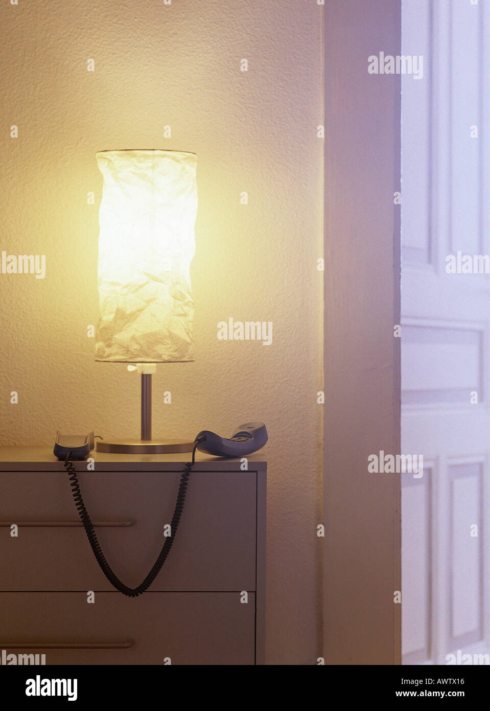 Phone off hook next to lamp on top of chest of drawers - Stock Image