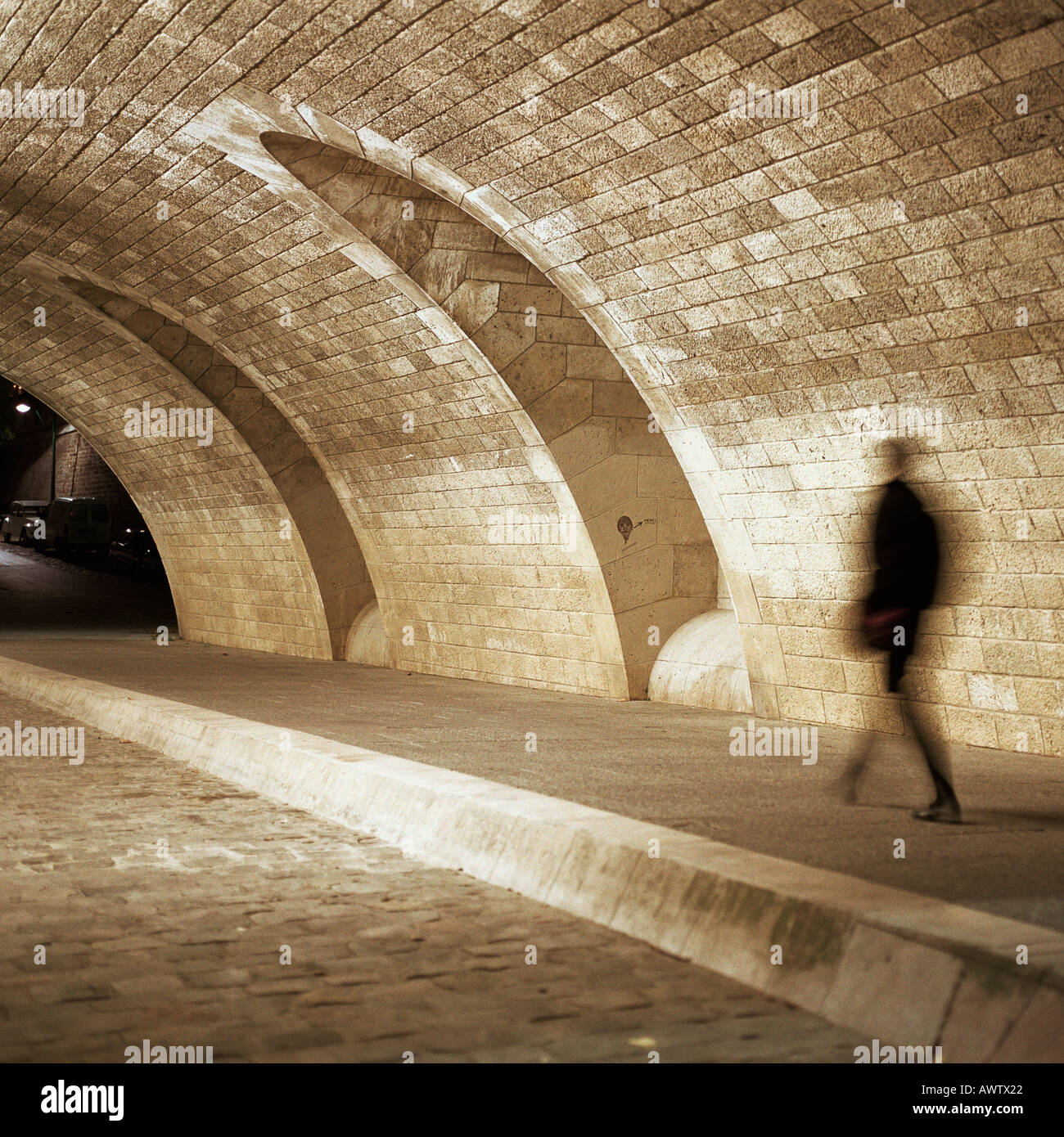 Person walking through tunnel at night Stock Photo