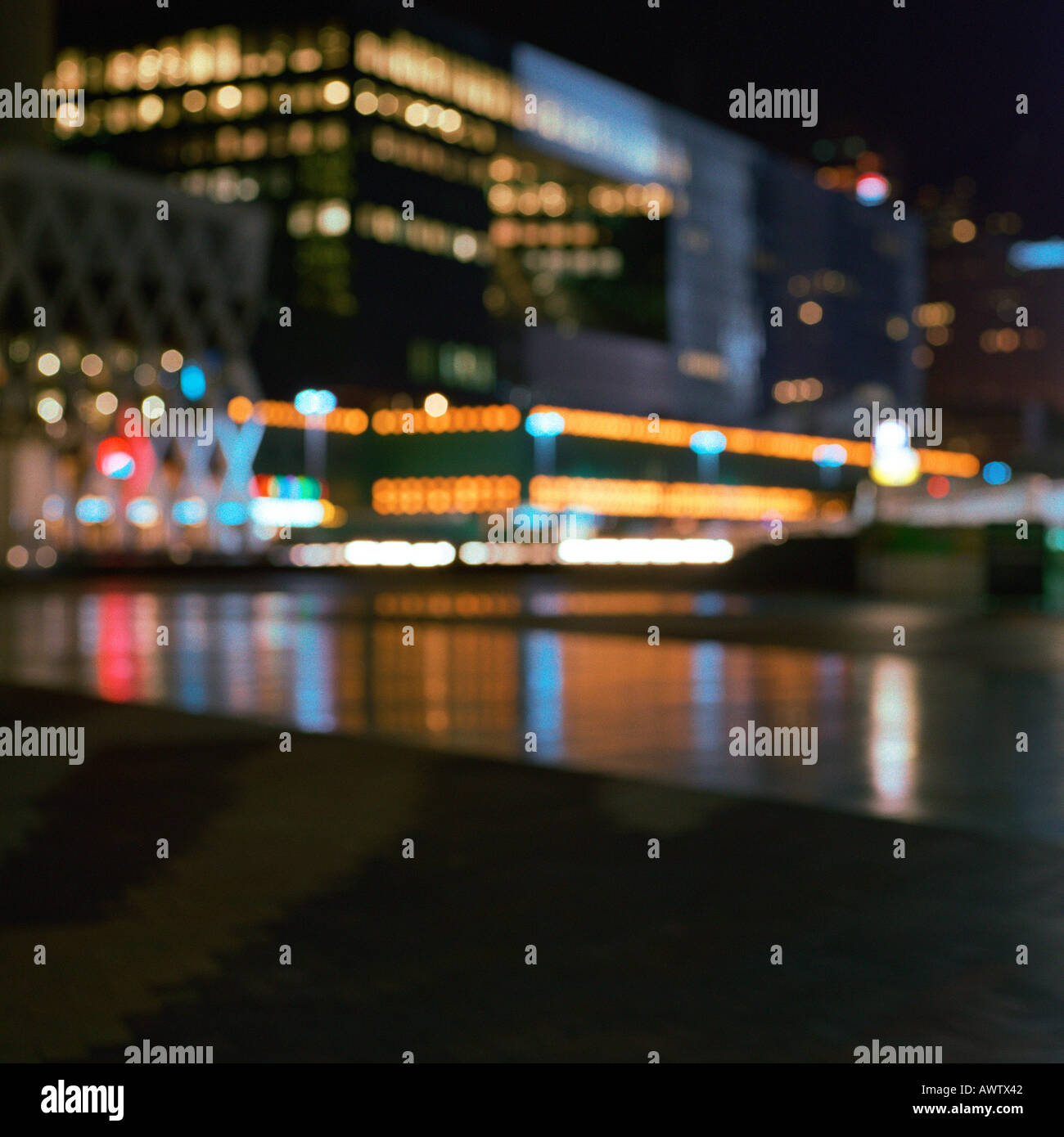 Office buildings lit up at night, exterior, long exposure. - Stock Image