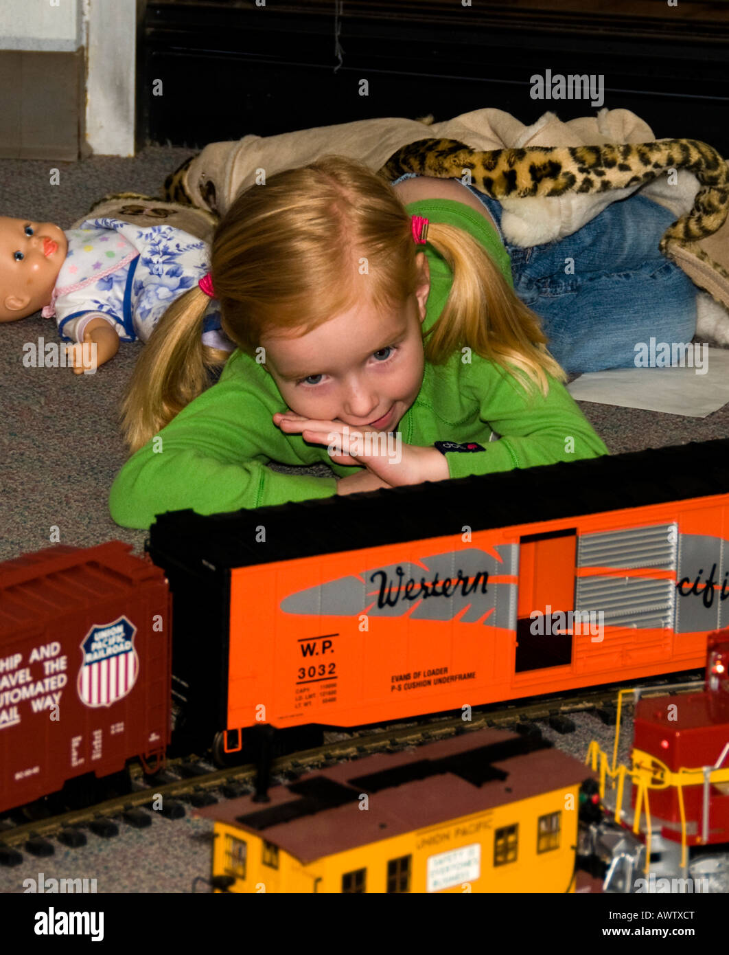 A young girl watched a miniature train run on a track at a train show Stock Photo