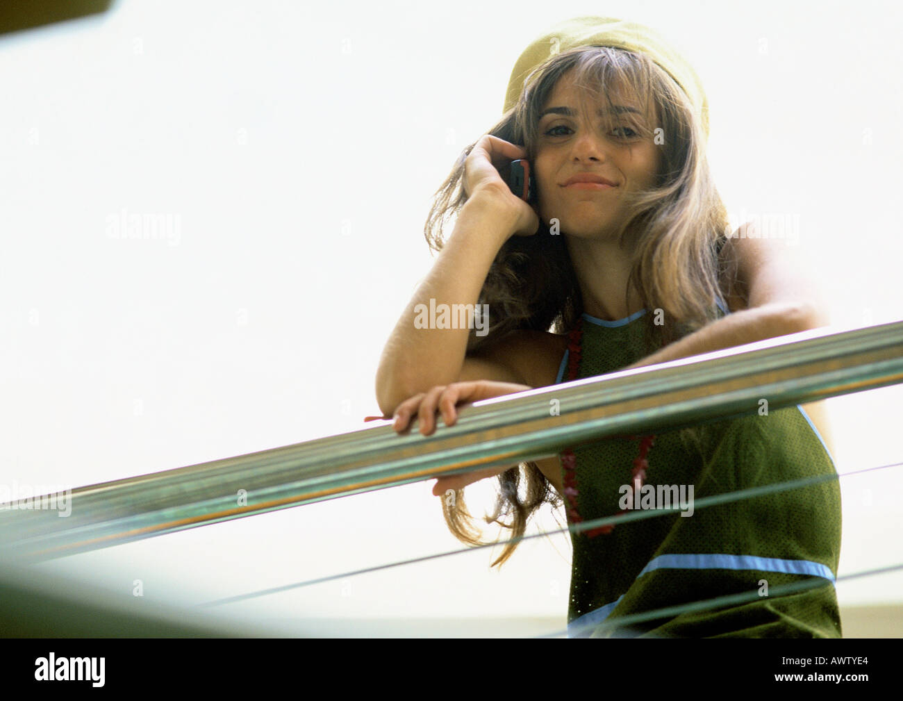 Woman leaning on arm rail talking on cell phone, low angle view - Stock Image