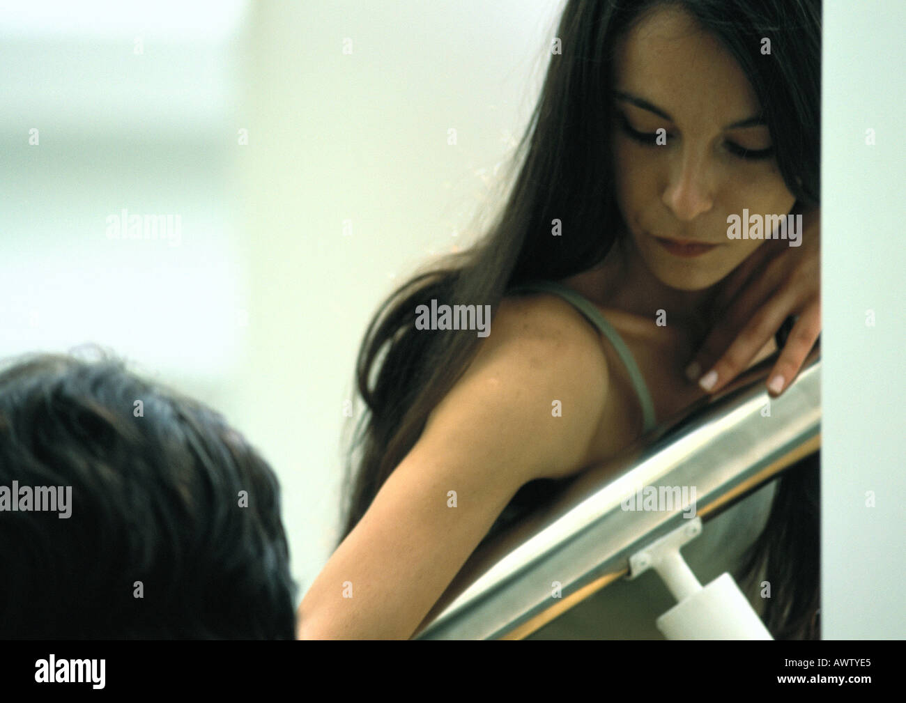 Woman resting head on arm rail, looking at someone - Stock Image