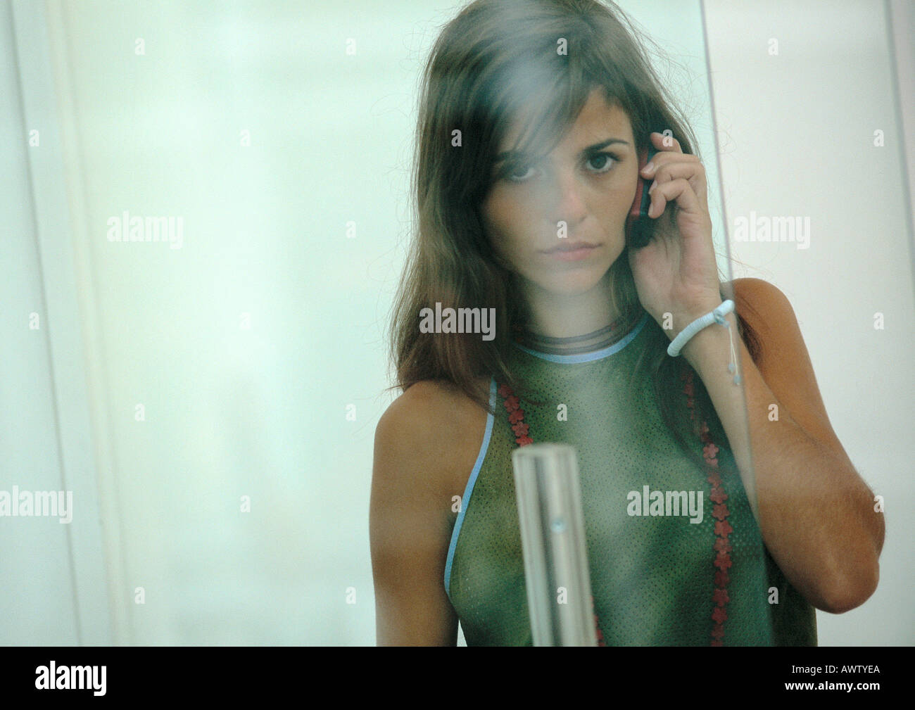 Woman on cell phone, view through glass - Stock Image