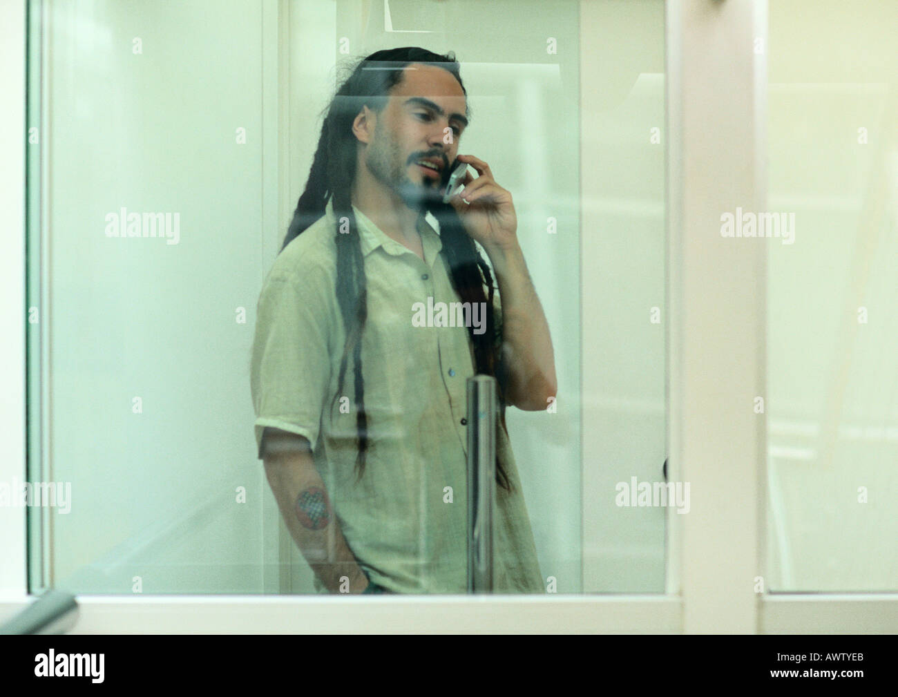 Man on cell phone, view through glass - Stock Image