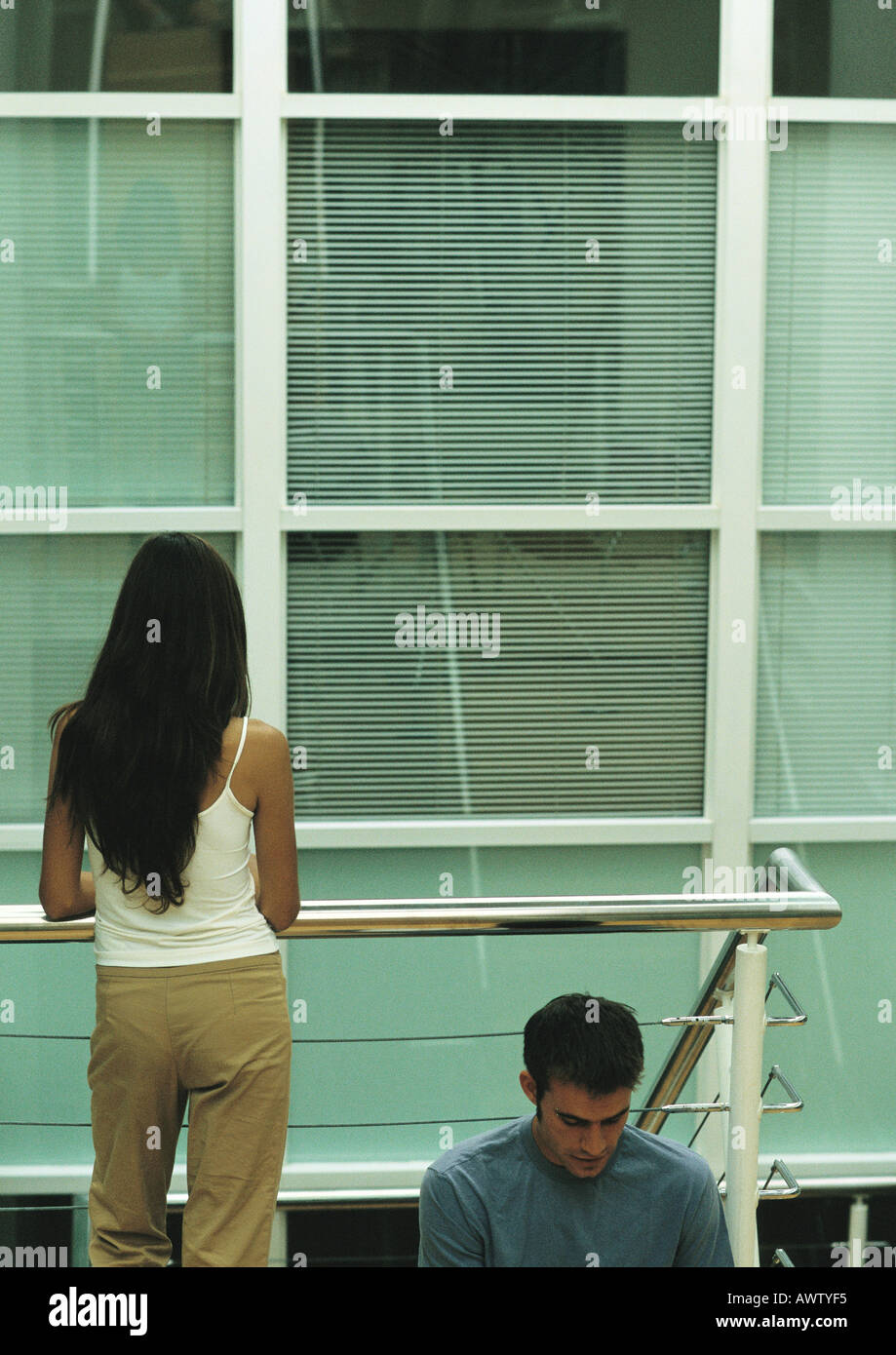 Man sitting, leaning against metal rails, and woman standing next to him, rear view - Stock Image
