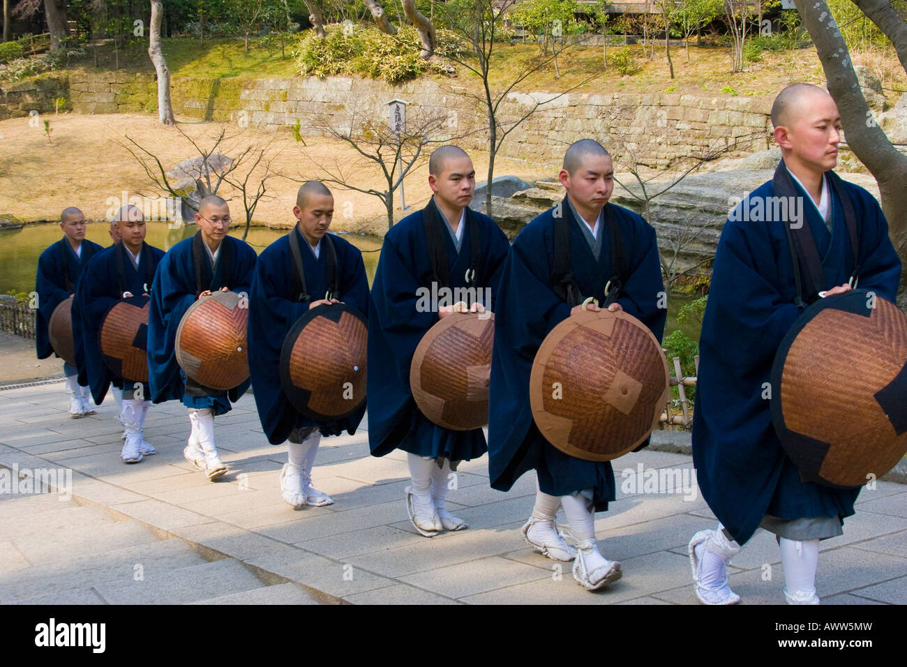 Monks in blue robes walking in a row in the Zen Buddhist Temple of Engakuji in Kamakura Japan - Stock Image