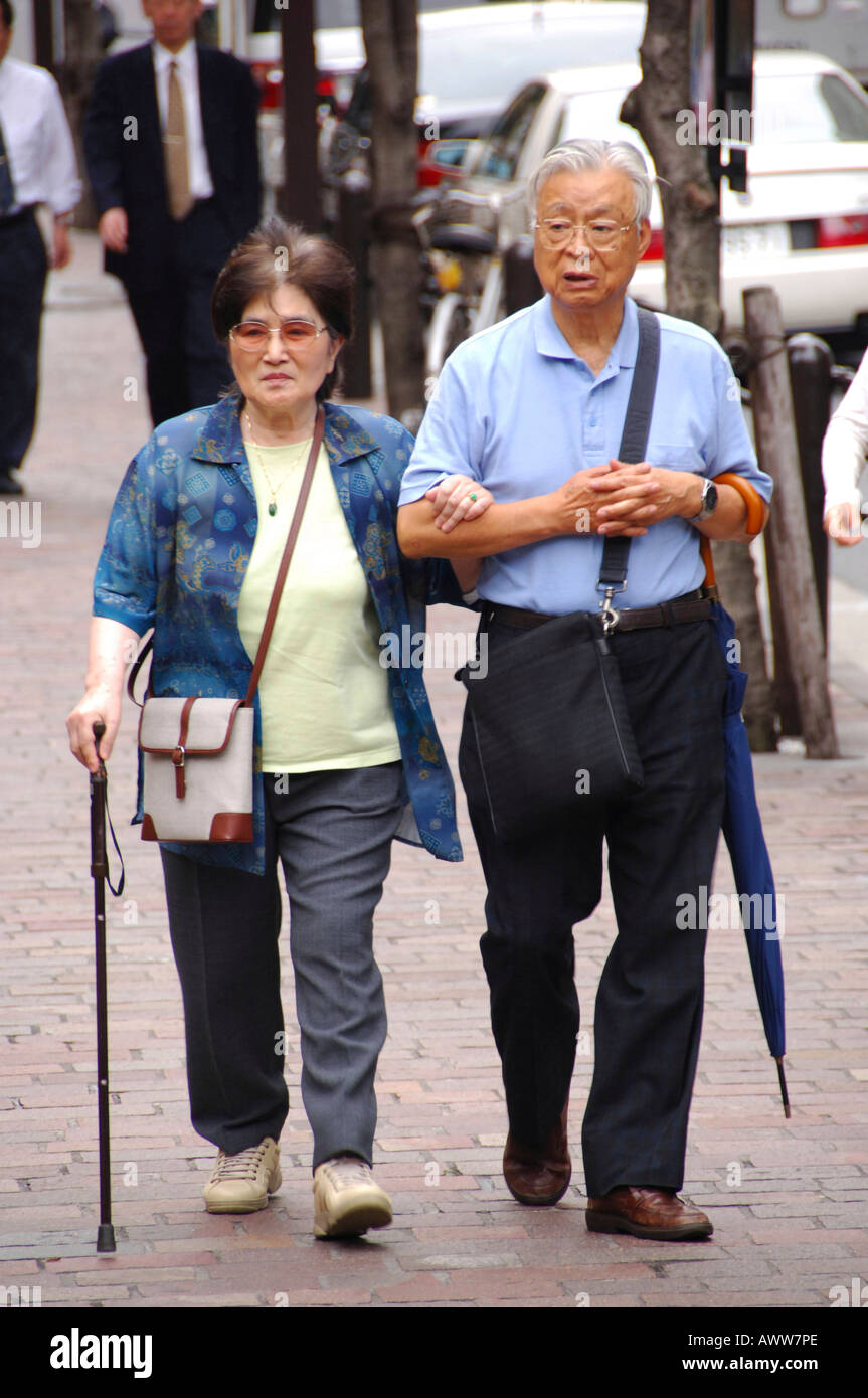 Old Japanese couple walking in Tokyo Stock Photo