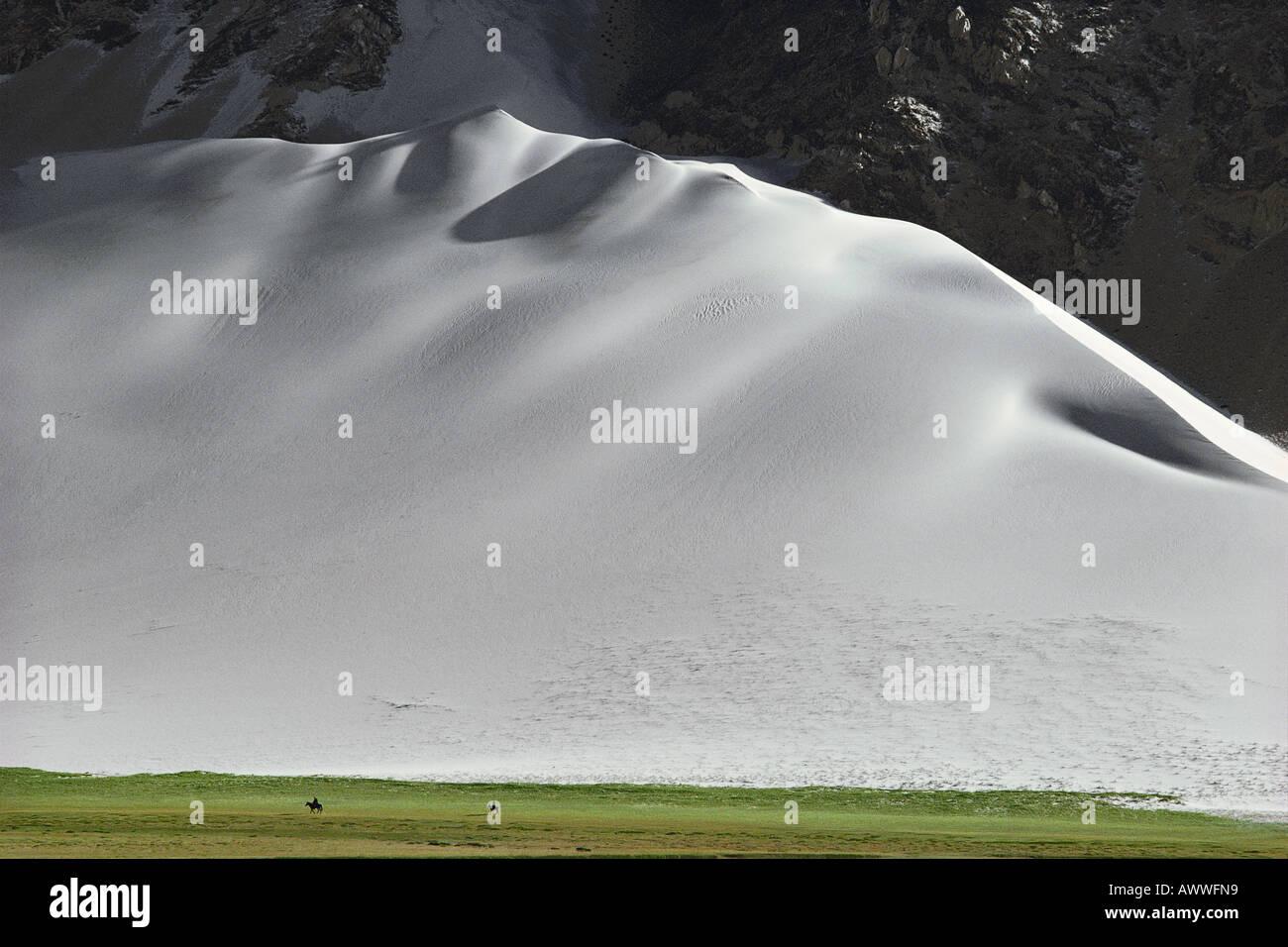 Horsemen beneath giant sand dune Pamir Range China 1980 - Stock Image