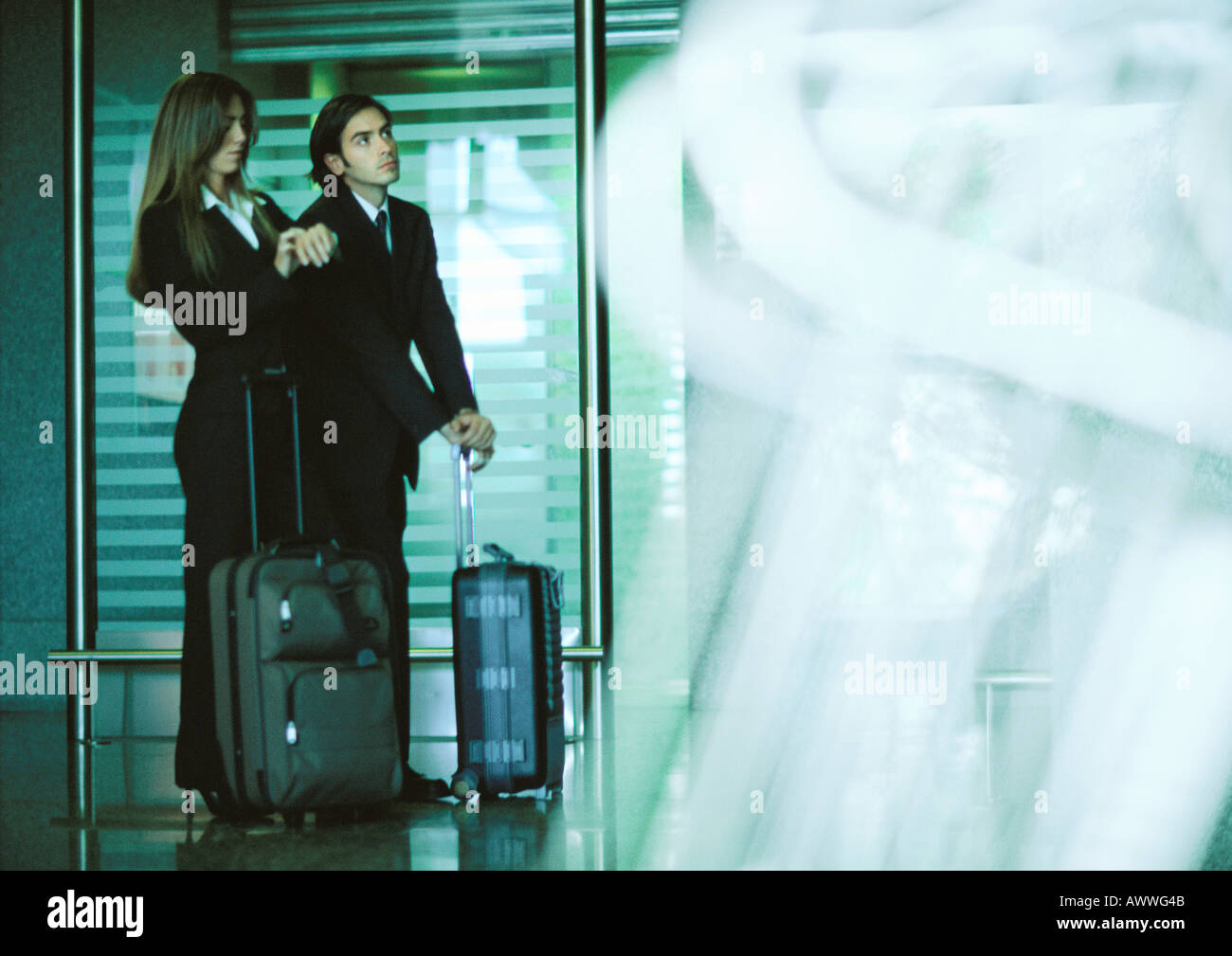 Man and woman standing with suitcases, woman looking at watch. - Stock Image