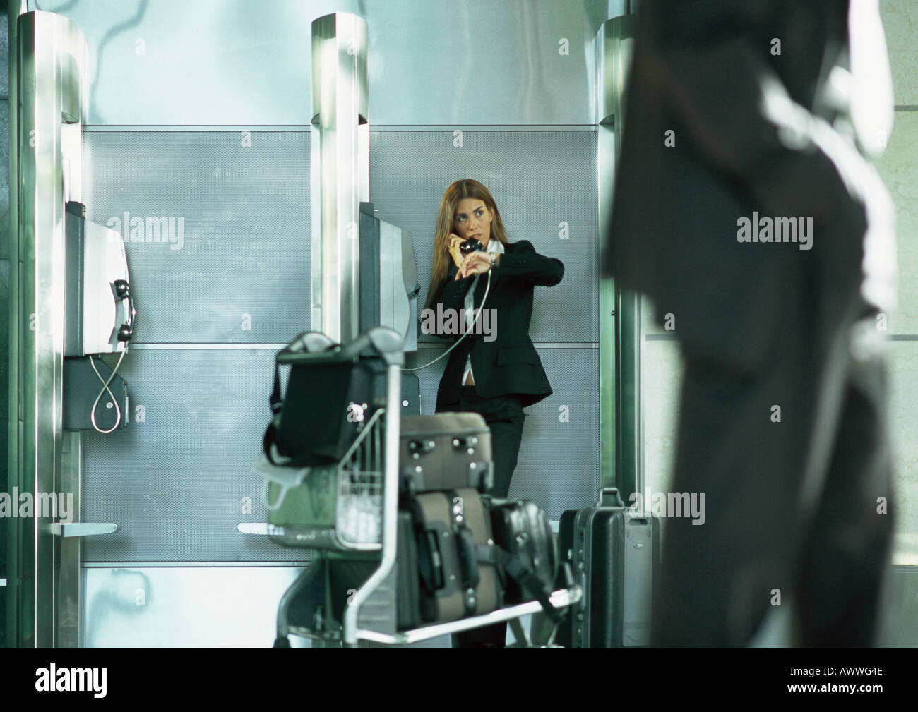 Businesswoman talking on public pay phone in airport - Stock Image