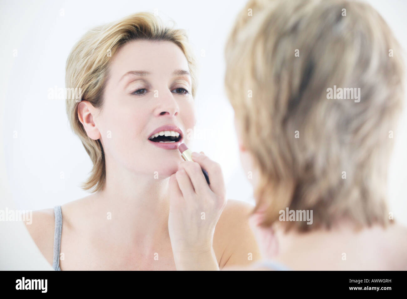 A woman applying lipstick in the mirror Stock Photo