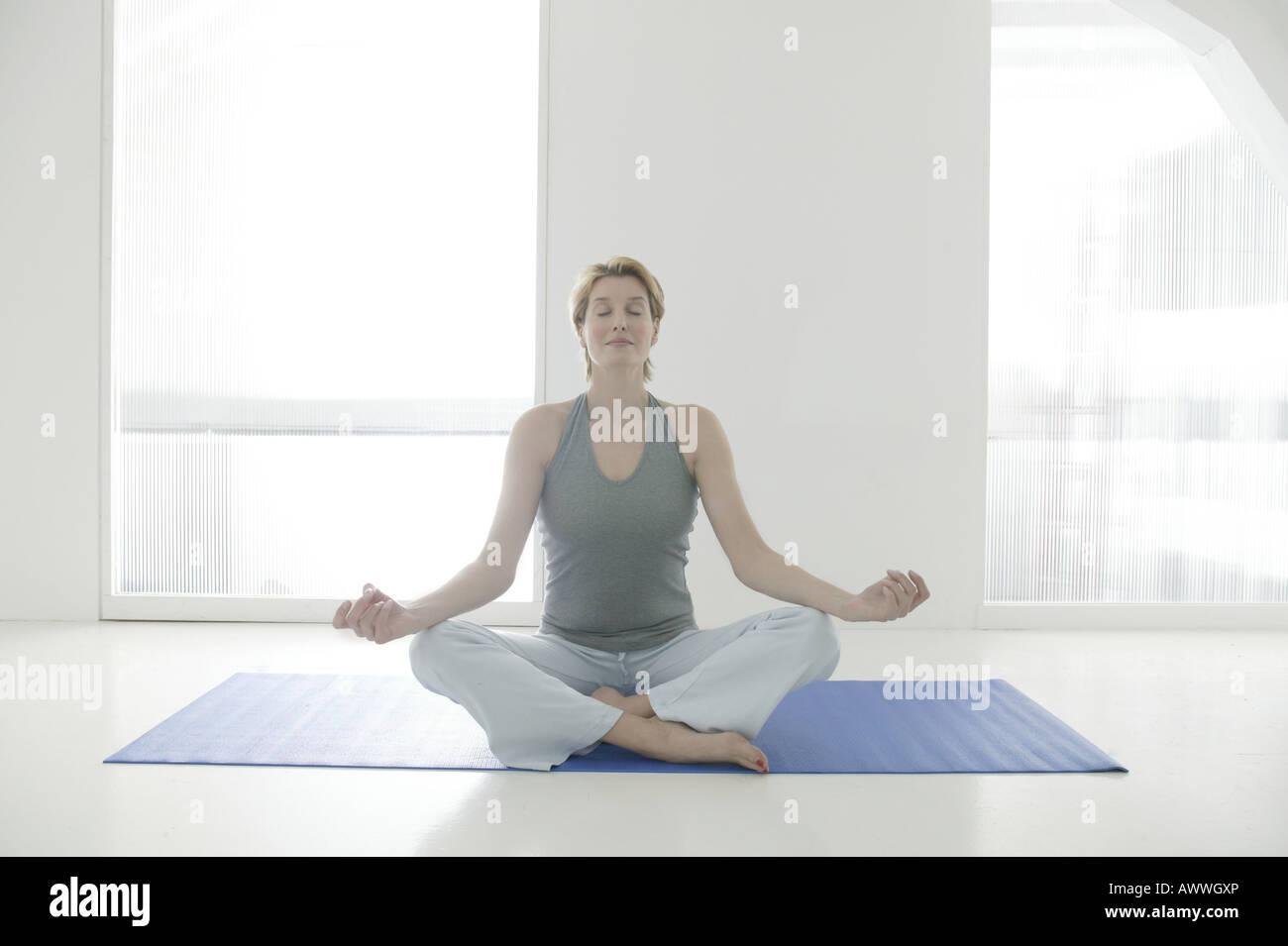 A woman sitting cross legged on a yoga mat meditating - Stock Image