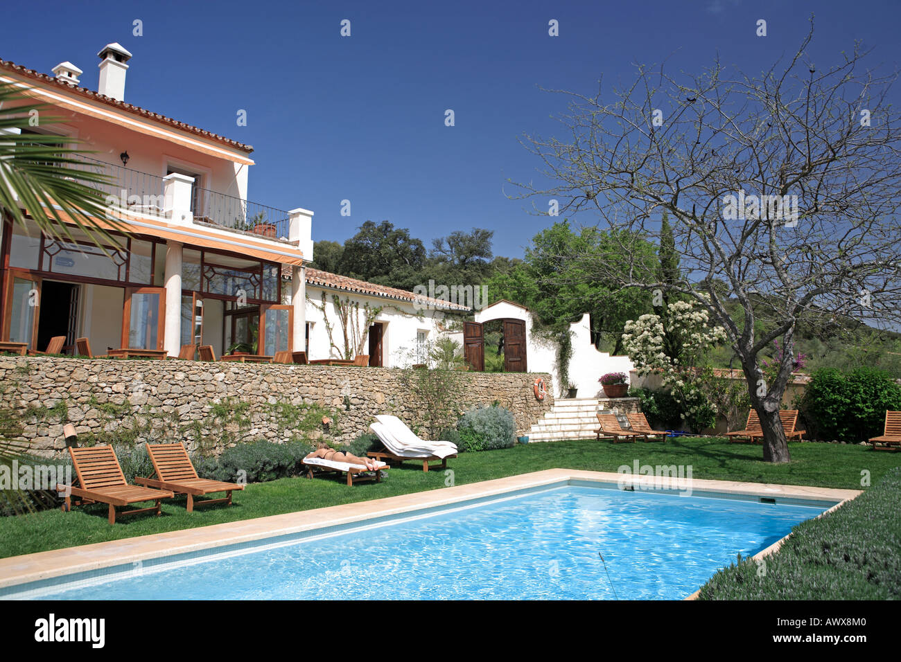 Large rustic hotel and swimming pool set in beautiful gardens in the Spanish countryside - Stock Image