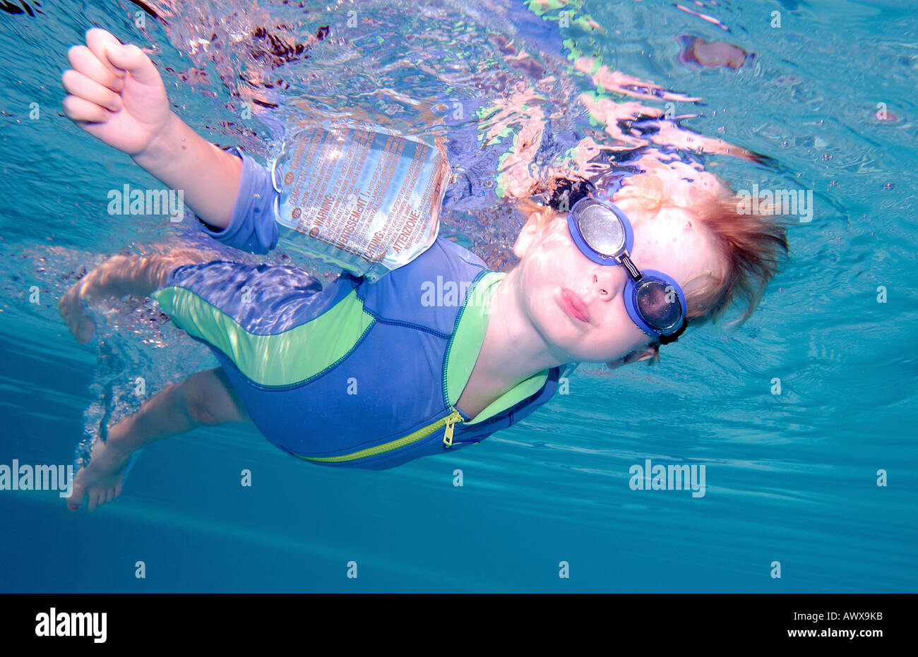 Young boy or child swimming underwater and holding breath with goggles on - Stock Image