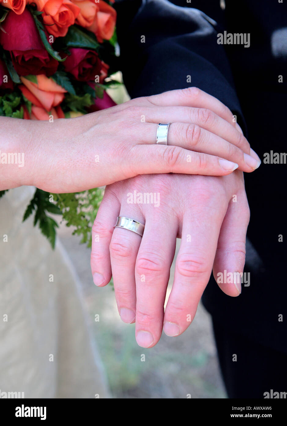 Newly weds hands showing off wedding rings and bouquet of flowers ...