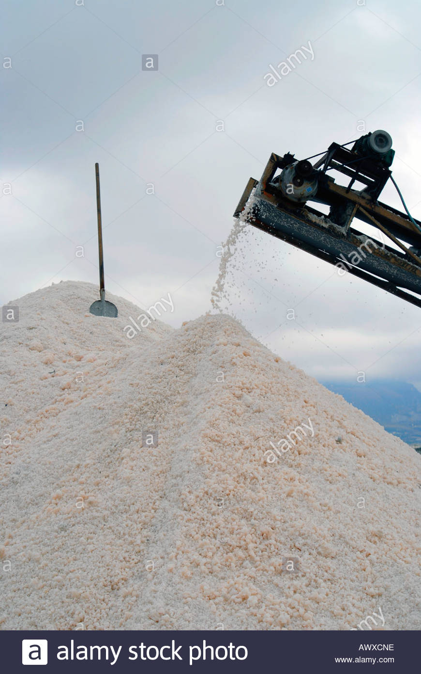 The end of a conveyor belt unloading salt from the saline onto a pile Trapani Sicily Italy - Stock Image