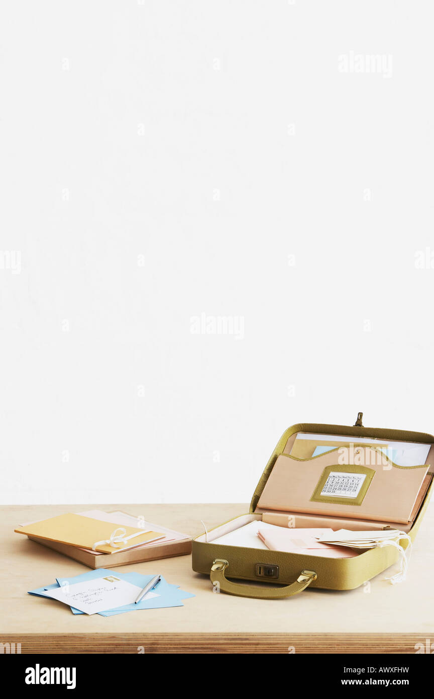 Postcard and envelopes next to suitcase with stationery items, elevated view, studio shot - Stock Image