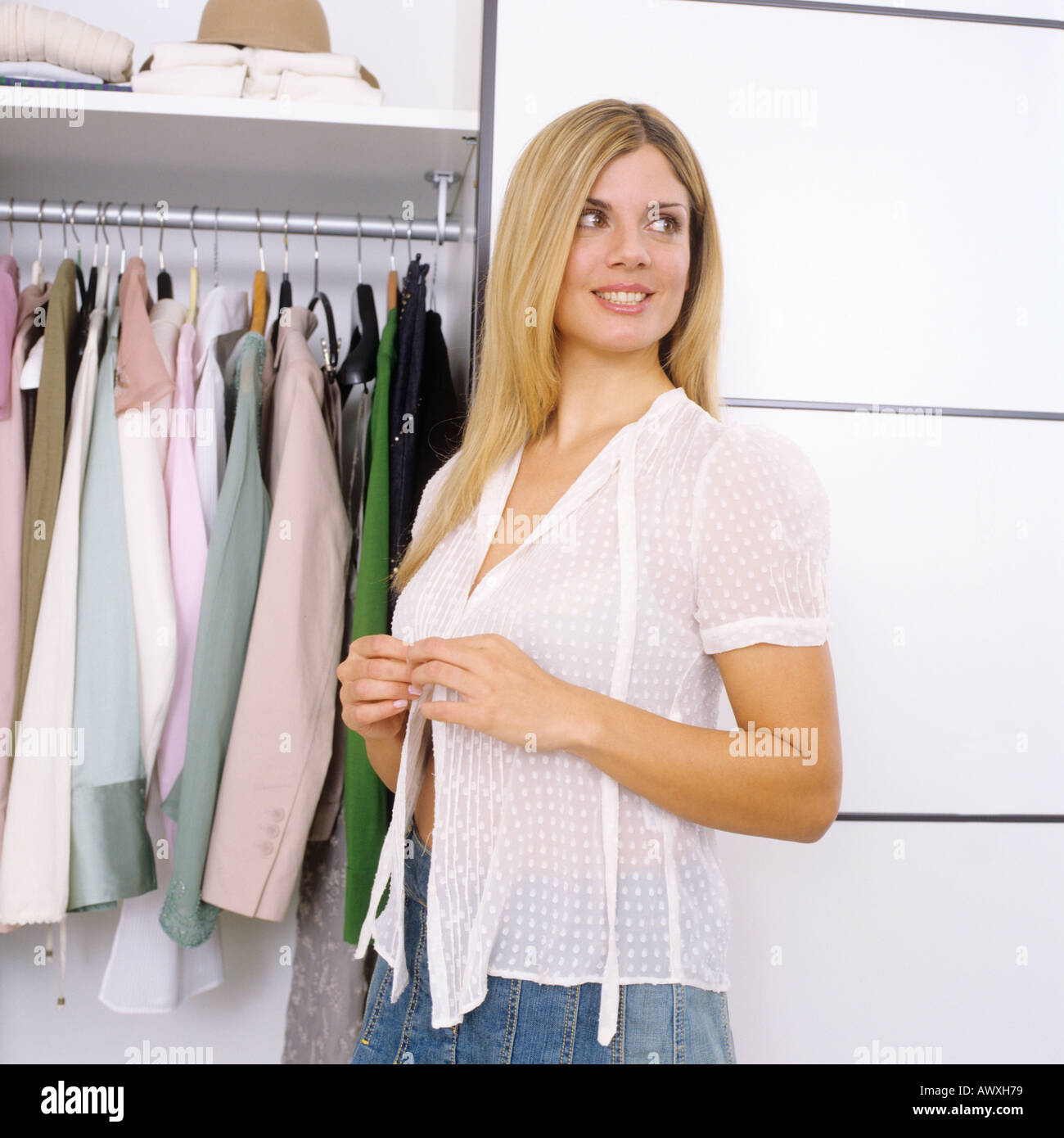 woman getting dressed in white blouse in front of closet