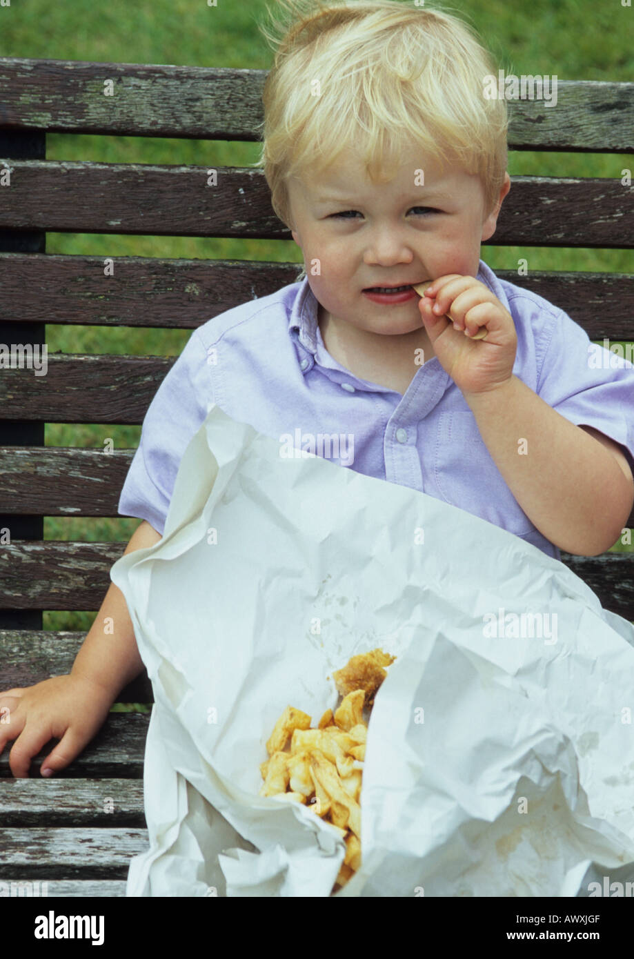 Young Boy Eating Chips At Southwold in Suffolk Uk - Stock Image
