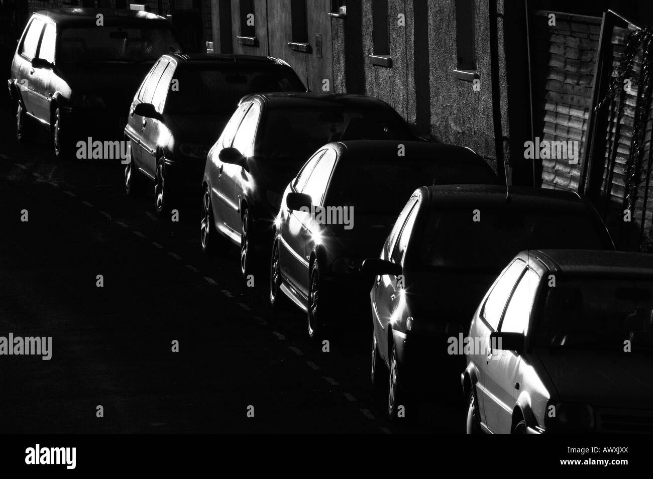 A line of parked cars reflect the early morning sun. - Stock Image