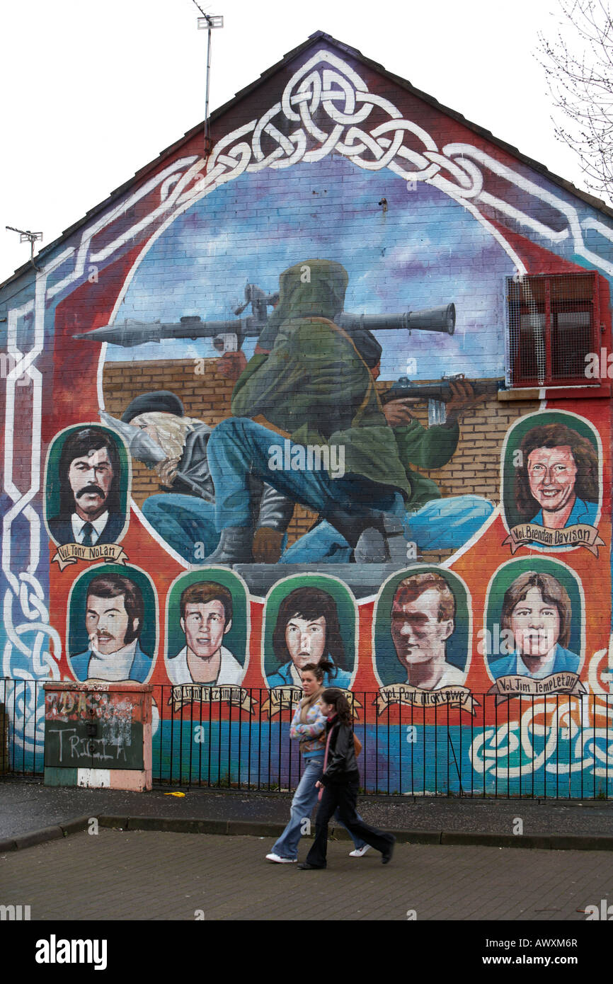 two young women walk past an IRA paramilitary memorial mural featuring RPG and IRA sniper in the markets area of Stock Photo