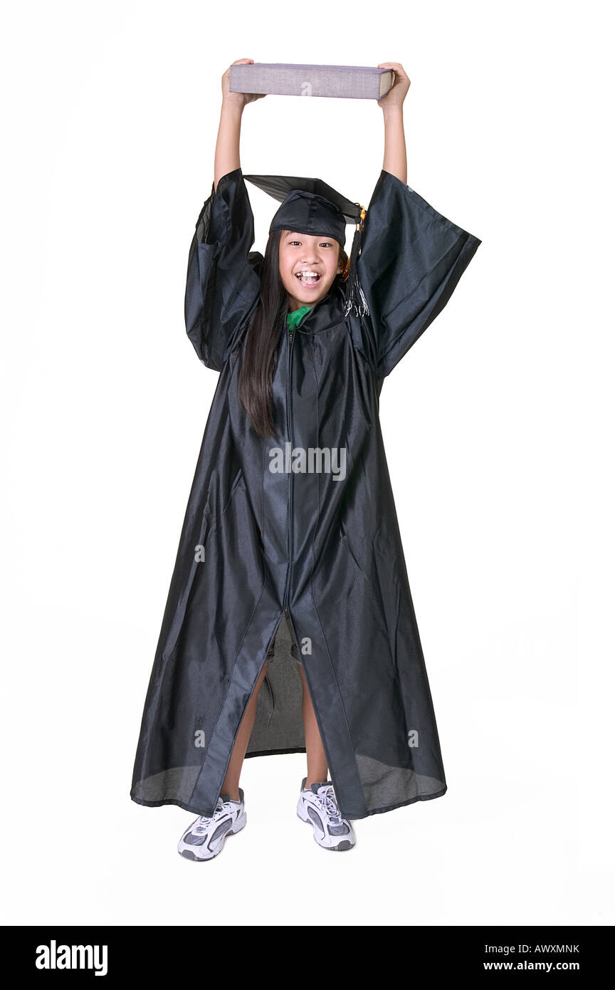Young Girl in Graduation Gown Lifting Book Over Her Head Stock Photo ...