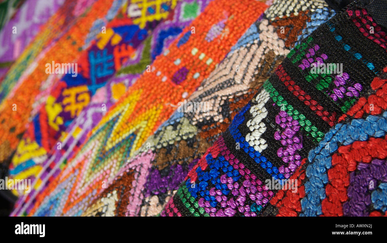 Market stall display of brightly brocaded textiles. As sold in popular tourist spots in Guatemala - Stock Image