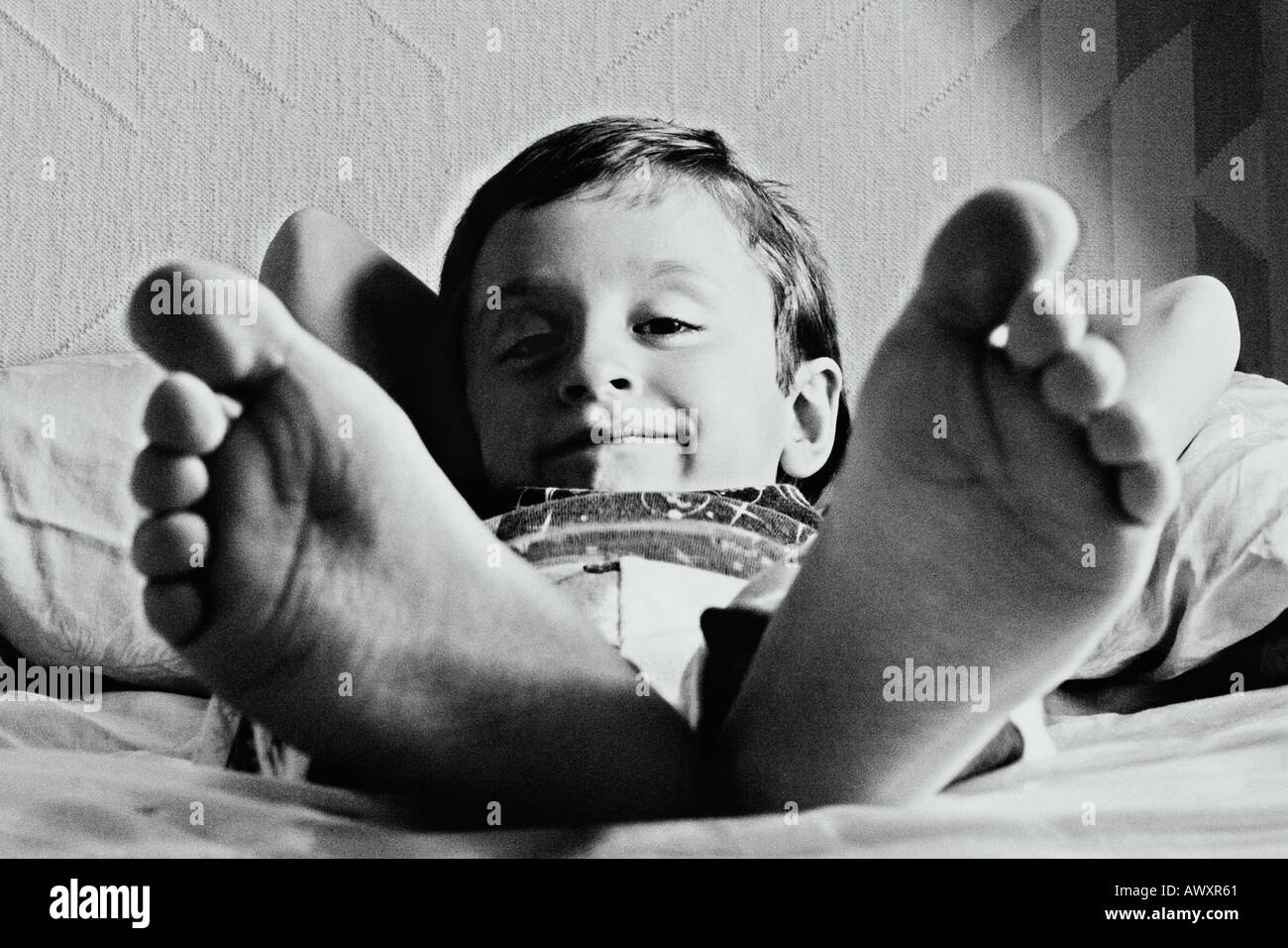Little Boy Lying In Bed With Big Giant Feet Stock Photo