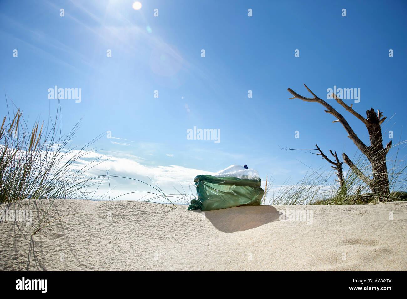 Rubbish bag on sand dune - Stock Image