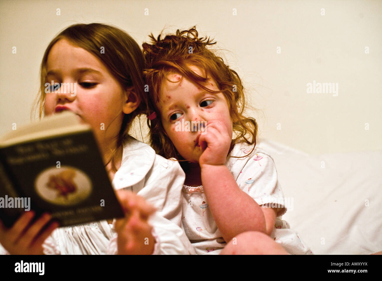 Girl with chicken pox listening to her big sister reading a bedtime story - Stock Image
