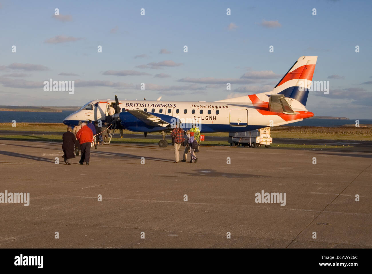 dh  KIRKWALL AIRPORT ORKNEY Passengers boarding BA aeroplane Saab 340 on runway british airways 340b Stock Photo