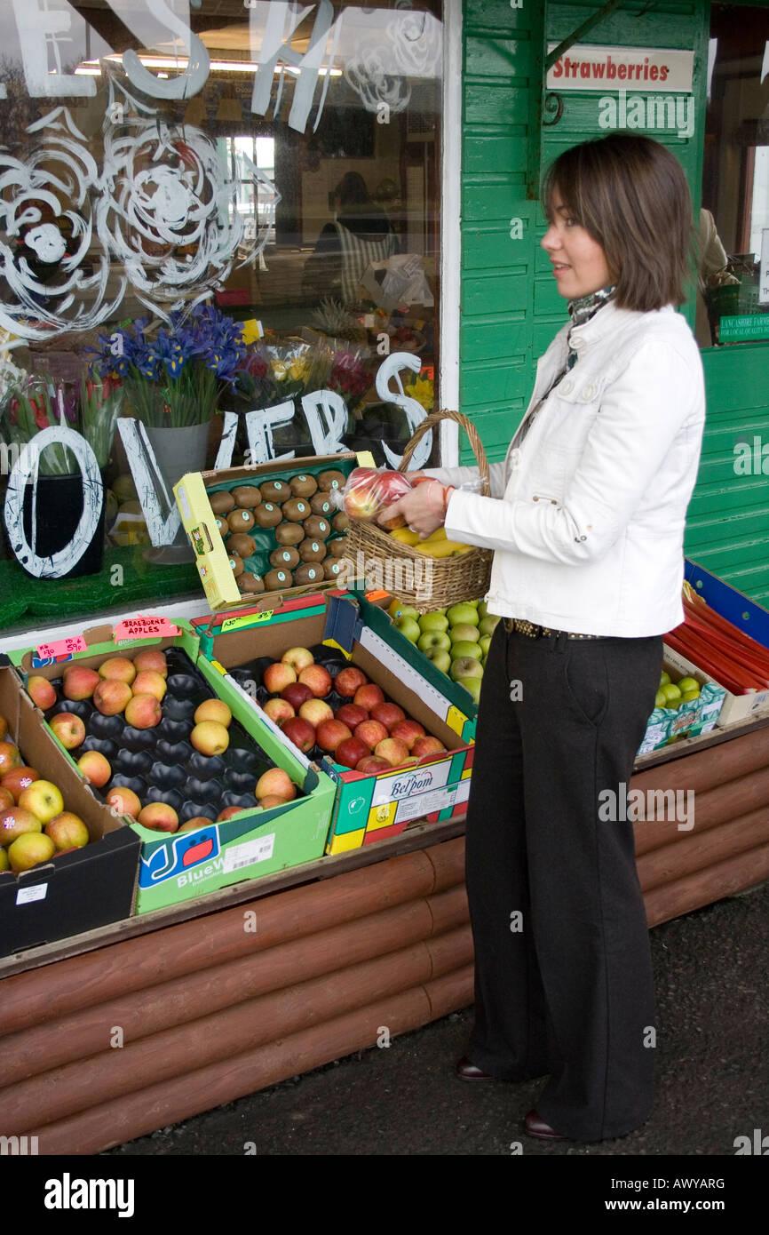 Woman buying vegetables and picking fruit from farm shop and fruit _ Tarleton Lancashire, uk - Stock Image