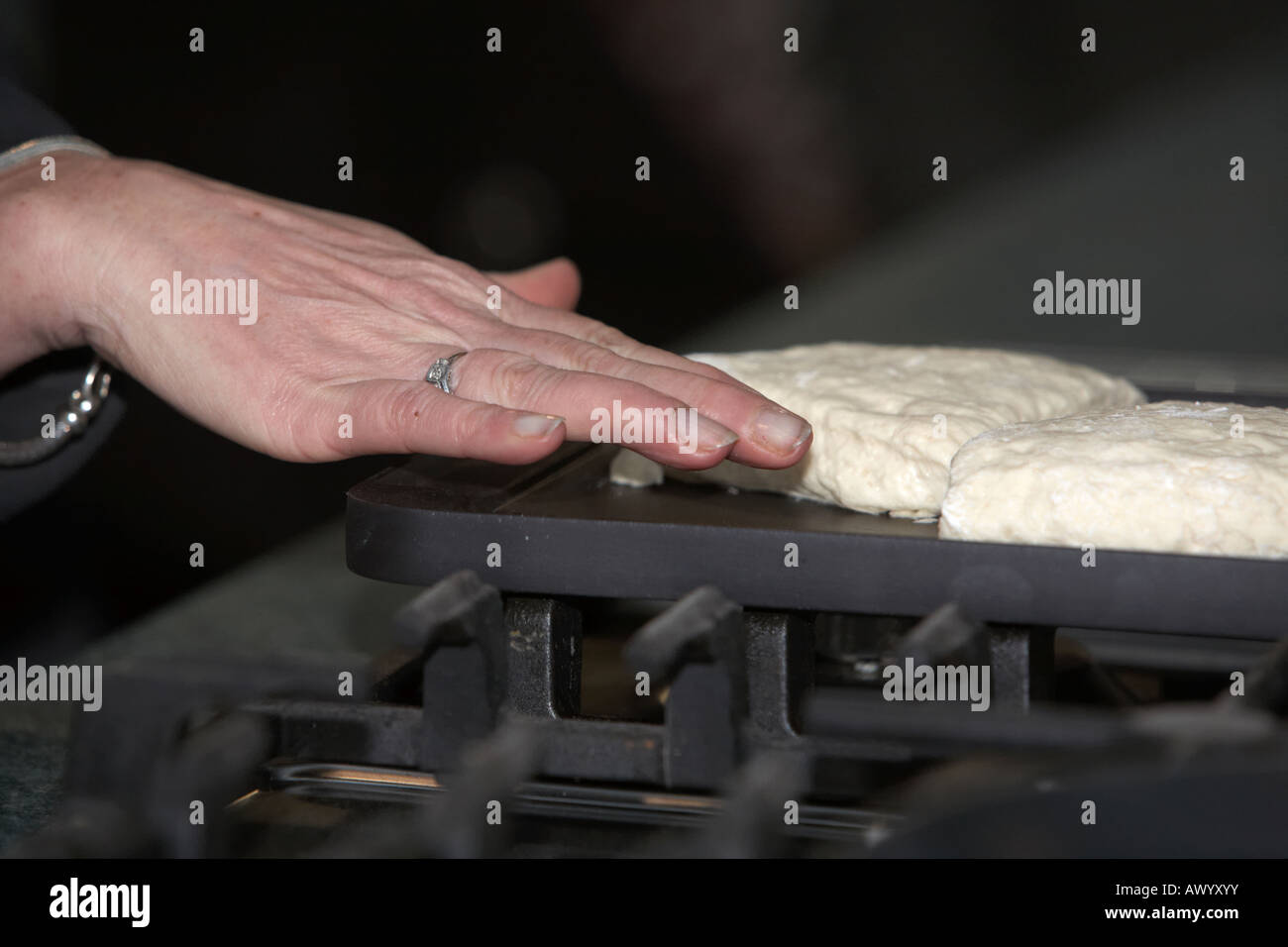 womans hand testing temperature of griddle cooking traditional irish soda bread - Stock Image