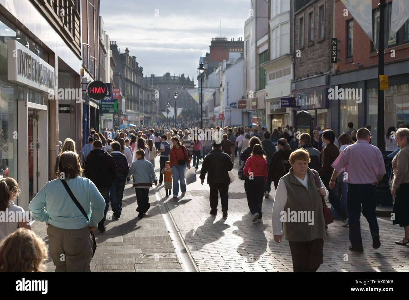 Urban Christmas Shoppers silhouetted in the busy Streets of Dundee, city centre, Tayside, Scotland, UK. People silhouettes against the low winter sun. - Stock Image