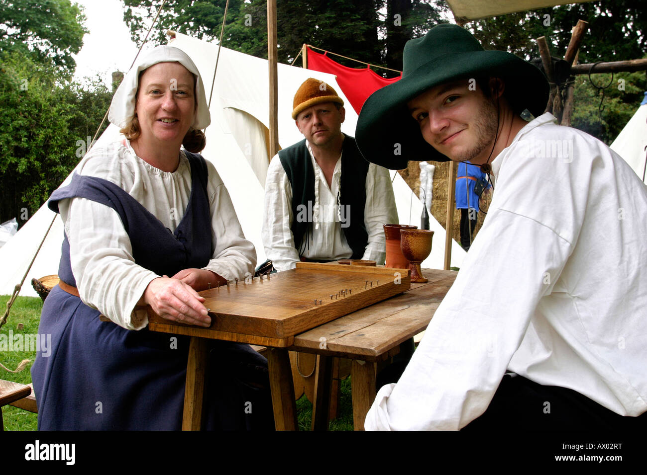 UK Worcestershire Evesham medieval fair people in costume playing shove groat board game - Stock Image